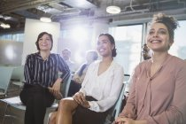 Smiling businesswomen listening in meeting at office — Stock Photo