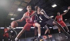 Молодые баскетболисты играют на площадке в гимназии — стоковое фото