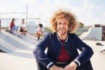 Портрет уверенный молодой человек с афро в солнечном скейт-парке — стоковое фото
