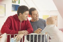 Male gay parents watching baby son in crib — Stock Photo