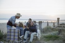Mature couples barbecuing, drinking wine on sunset beach — Stock Photo