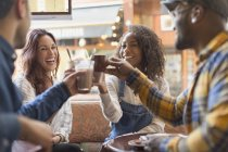 Smiling friends toasting coffee cups in cafe — Stock Photo