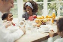Многоэтнического молодой семьи едят завтрак за столом — стоковое фото