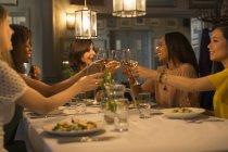 Women friends toasting white wine glasses at restaurant table — Stock Photo
