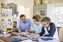 Mi homme adulte aider les adolescents à faire leurs devoirs à table — Photo de stock