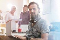 Усміхнений чоловік дизайн Професійний портрет з навушниками, використовуючи ноутбук у office — стокове фото