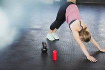 Молода жінка, розтягування в низхідній облицювальні собака йога поза, в тренажерний зал — стокове фото