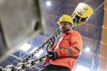 Сталевар держит крановую цепь на заводе — стоковое фото