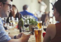 Couple with cell phone talking and drinking beer and wine at restaurant table — Stock Photo