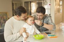 Male gay parents feeding baby son in kitchen — Stock Photo