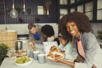 Portrait smiling mother eating breakfast toast with young family in kitchen — Stock Photo