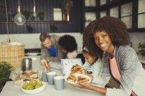 Porträt lächelnde Mutter Essen Frühstück Toast mit jungen Familie in Küche — Stockfoto