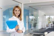 Porträt lächelnde Geschäftsfrau mit Ordnern im Konferenzraum — Stockfoto
