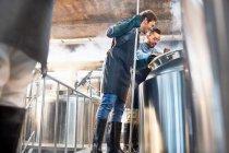 Männliche Brauer Überprüfung Mehrwertsteuer in Brauerei — Stockfoto