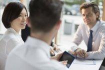 Uomini d'affari con tablet digitale che parlano in riunione — Foto stock