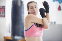 Young female boxer stretching shoulder and arms in gym — Stock Photo