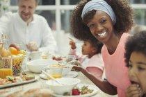 Портрет улыбается матери, заказывающего завтрак с молодой семьей за столом — стоковое фото