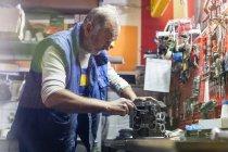 Senior-Motorradmechaniker repariert Motorteil in Werkstatt — Stockfoto