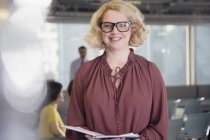 Портрет посміхаючись, впевнена в собі бізнес-леді з документами в офісі — стокове фото