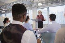 Businesswoman at podium leading conference presentation — Stock Photo