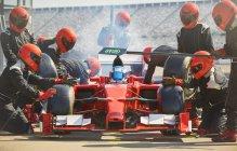 Équipage de fosse travaillant sur la formule une voiture de course dans pit lane — Photo de stock