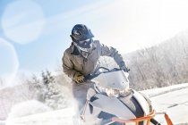 Man riding snowmobile in sunny snowy field — Stock Photo