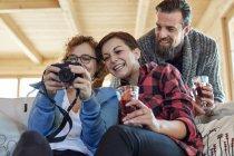 Друзья смотрят на фотографии на цифровой камере и пьют горячий тодди в хижине — стоковое фото