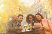 Lächelnd Freunden Bier trinken und nehmen Selfie mit digital-Tablette in Herbst Straßencafé — Stockfoto