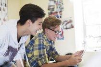 Due ragazzi adolescenti si divertono mentre usano il tablet digitale in camera — Foto stock