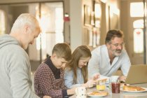Male gay parents and children eating breakfast and using laptop and digital tablet at kitchen counter — Stock Photo