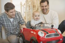 Male gay parents and baby son playing with toy car — Stock Photo