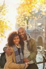 Portrait smiling, affectionate couple hugging along sunny autumn canal — Stock Photo