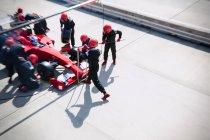 Яма екіпажем заміни шин на формули один гоночний автомобіль в піт-лейн — стокове фото