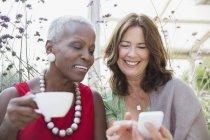 Улыбаясь Зрелые женщины друзей пить кофе и с помощью мобильного телефона — стоковое фото