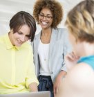 Equipe de escritório feminino usando laptop, conversando e sorrindo — Fotografia de Stock