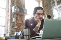 Junge männliche Designer mit Laptop in Werkstatt — Stockfoto