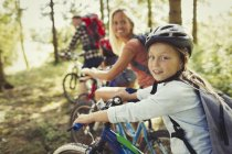 Portrait mother and daughter mountain biking in woods — Stock Photo