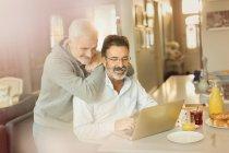 Чоловічий гей-пара, використовуючи ноутбук на сніданок кухонного столу — стокове фото