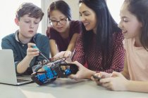 Female teacher and students programming and assembling robotics in classroom — Stock Photo