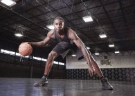 Portrait confident young male basketball player dribbling the ball on court in gymnasium — Stock Photo