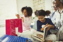 Родители смотрят, как дочери открывают подарок на день рождения в постели — стоковое фото