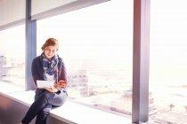 Geschäftsfrau nutzt digitales Tablet und trinkt Kaffee am sonnigen städtischen Bürofenster — Stockfoto