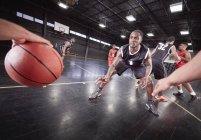 Молодые мужчины баскетболистов игры на суде в гимназии — стоковое фото