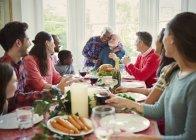 Affectionate multi-ethnic senior couple hugging at family Christmas dinner table — Stock Photo