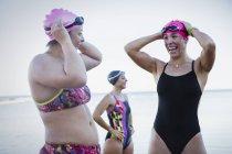 Улыбаясь женщин открытой воде пловцов, регулируя плавание пробки в океане — стоковое фото