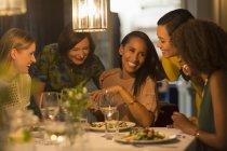 Улыбающиеся друзья празднуют день рождения женщины за ресторанным столом — стоковое фото