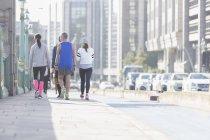 Läufer laufen auf sonnigem städtischen Bürgersteig — Stockfoto