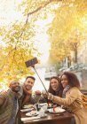 Smiling friends taking selfie with selfie stick at autumn sidewalk cafe — Stock Photo