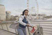 Portrait smiling woman bike riding on bridge over Thames River near Millennium Wheel, London, UK — Stock Photo
