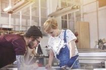 Les concepteurs examinent les plans à l'ordinateur portable dans l'atelier — Photo de stock